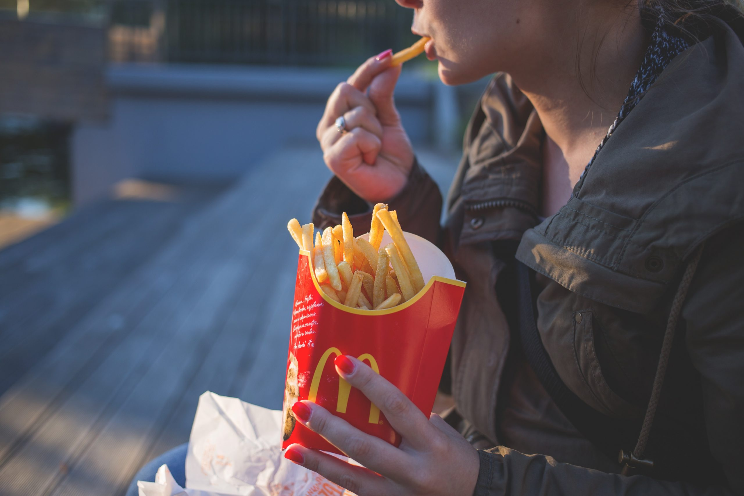 woman-in-brown-classic-trench-coat-eating-mcdo-fries-during-139681