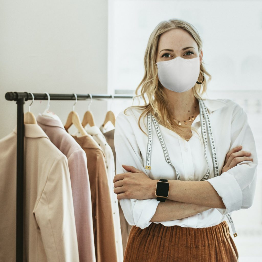 Designer in new normal boutique wearing mask, covid 19