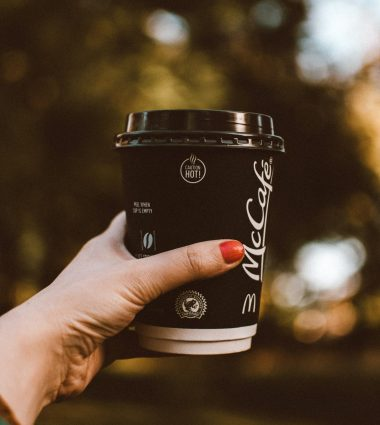 selective-focus-photo-of-woman-s-hand-holding-out-a-mccafe-3138487